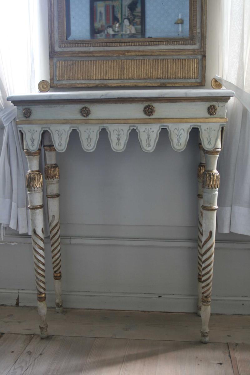 Speil med tilhørende konsollbord, hvitmalte med forgylt dekor og forsiringer.  To-delte speil, det lille speilfeltet øverst er dekorert med påmalt urnemotiv.