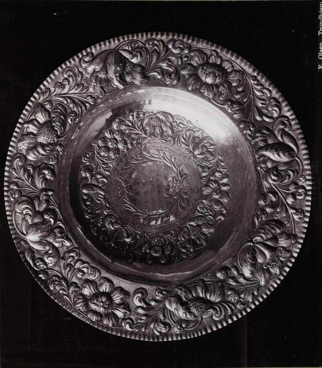 Dåpsfat, forsiret med dervet ladverk, fra 1694. Gitt til Vår Frue kirke i Trondheim, Nord Trøndelag. Den Nordenfjeldske kunstutstilling 1893.