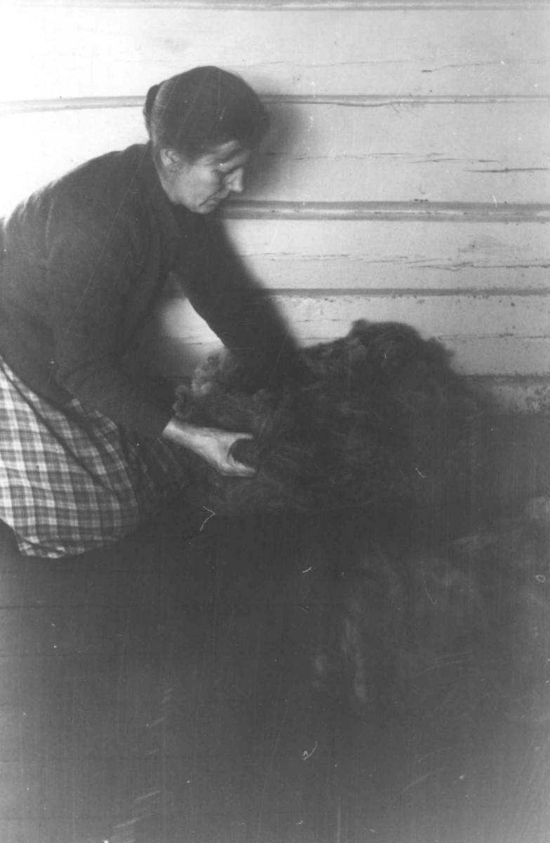 """""""Plukka ull"""". Gunnhild Smeland sitter med ull som er kardet en gang. Åseral, Vest-Agder 1943."""