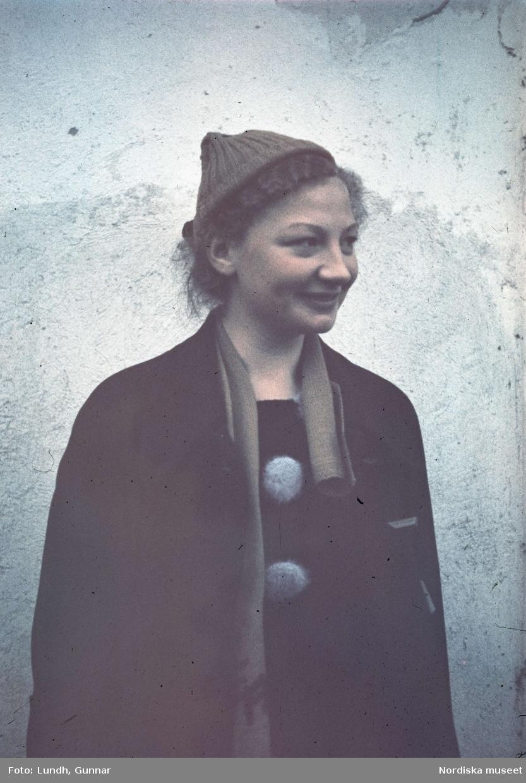 Friluftsklädd kvinna på svamputflykt, fotograferad mot vit husvägg.
