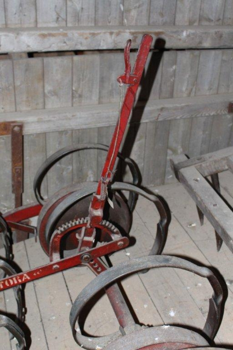 Ramme av vinkeljern. 11 tinder i 3 rader. To hjul i bakre rad, et mindre hjul fremst. Håndtak for regulering av arbeidshøyden.