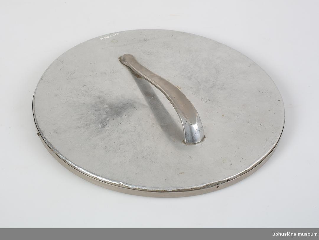 Rund spegel. Kant, sida och baksida av tenn.  Svängt tennhandtag på baksidan.  Föremål från Brorssons Damfrisering i Kungshamn, se UM023941.