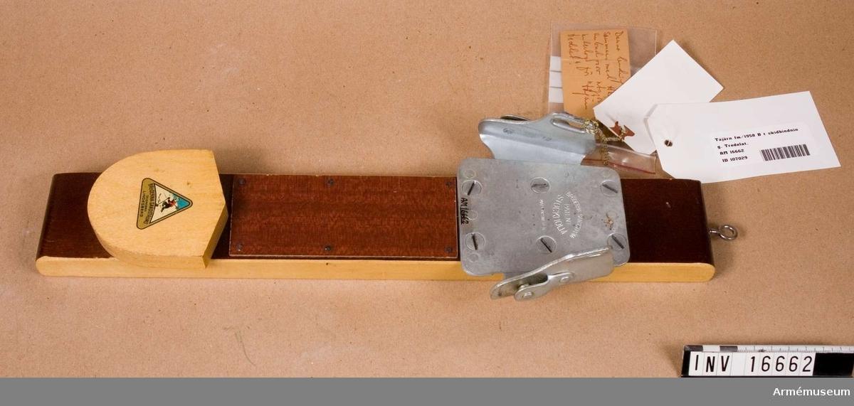"""Tåjärn m/1958 B t skidbindning. Tredelat.Metalldelarna är av varmförzinkat stål. Märkt """"Bröderna Sandtröm Patent Stockholm Made in Sweden"""". Längd och vikt med monteringskloss av trä.Etikett m text """"Skidbindning fm/58 B AB Bröderna Sandström Dnr 1898/58"""". Denna bindning har tillsammans med ABC-fab anbud prov utgjort underlag för """"tåjärn tredelat""""."""