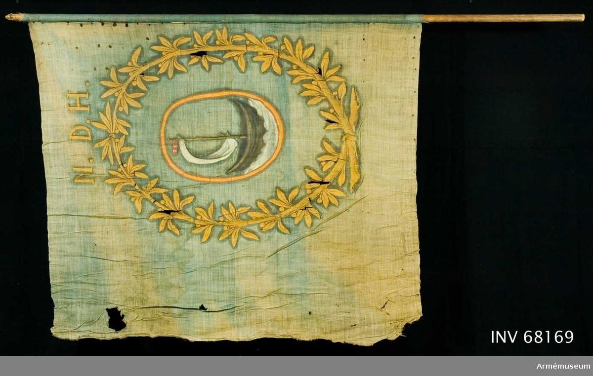 Duk: Tillverkad av enkel blå linnelärft, sammansydd av två horisontella våder. Riven i vertikala ytterkanten. I över- och underkanten (horisontella) stadkanten. Fäst med provisoriska järnnagel på en liten läderremsa.  Dekor: Målad endast på dukens rätta insida. En oval röd och gulkantad sköld, vari böljande vatten (vitaktigt) en seglande båt i brunsvart med vitt segel och röd vimpel. Vapnet omslutes av en upptill och nedtill hopknuten krans av två lagerkvistar med blad och bär, allt i gult. Längs överkanten bokstäver i gult.  Stång: Uppenbarligen flyttad. Stång tillverkad av trä, avsågad och brunmålad. Liten profilerad träknopp.