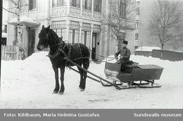 Man med häst och släde vid Nybrogatan 30. Huset bakom revs 1955.