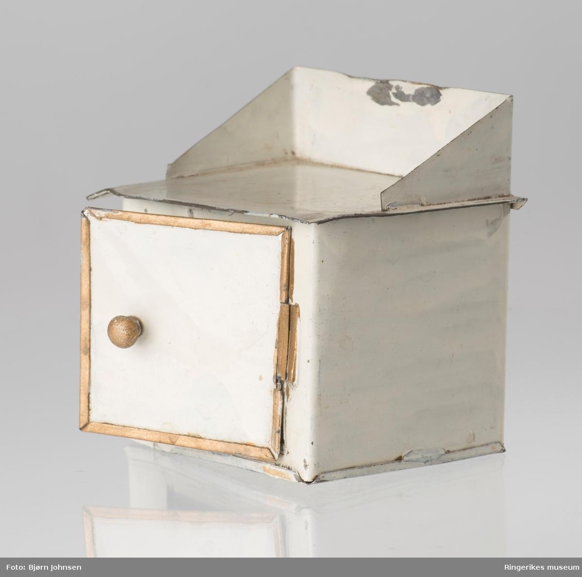 Dukkeutstyr, gryteskap som skulle stå nær komfyren. Rektangulær, mot kvadratisk med topplate, skrådd ryggplate og dør i front til å åpne. Liten dreibar knapp på skapdøren, stort rom innvendig. .