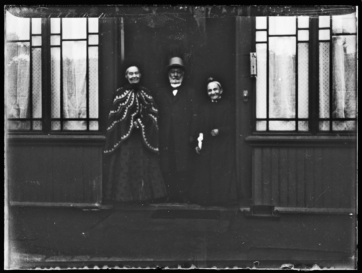 Haaken Christian Mathiesen og to damer står i en døråpning.