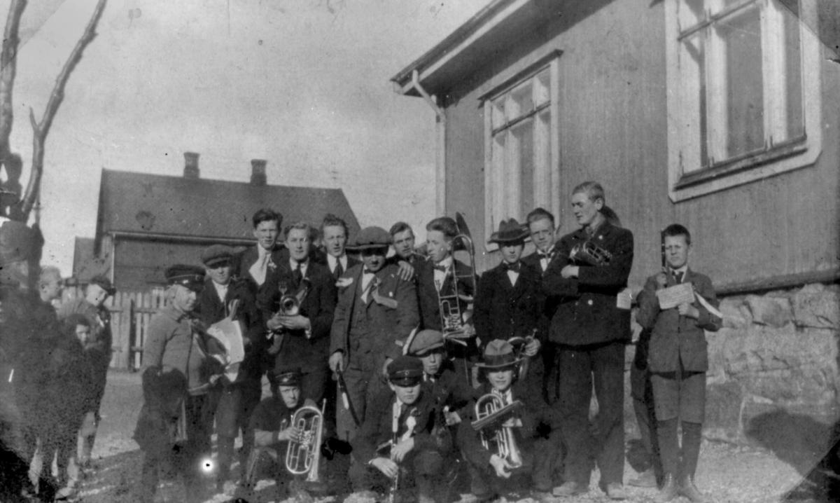 Kirkenes hornmusikk. 15 gutter og menn med instrumenter. Foto- grafert utendørs. Et par hus i bakgrunnen. Ingen årstall.