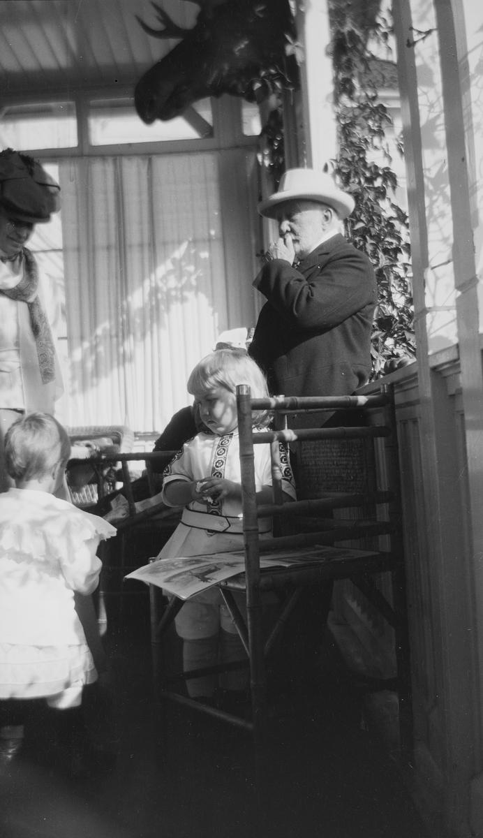 En uidentifisert kvinne og Haaken Christian Mathiesen står sammen med et uidentifisert barn og Iacob Ihlen Mathiesen på en veranda.