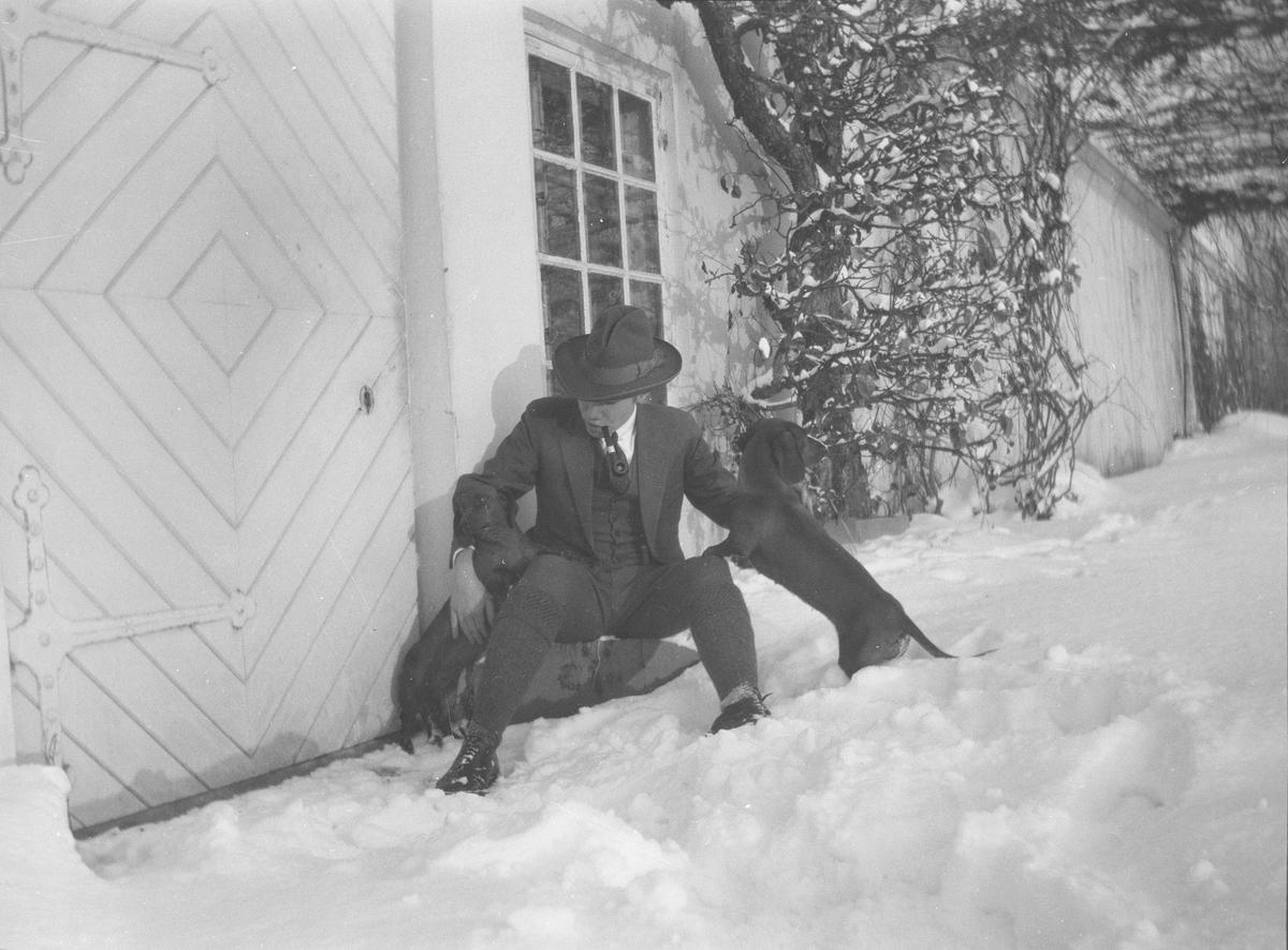 Iacob Ihlen Mathiesen sitter, på en stein eller lignende, utenfor en dør i grunnmuren til hovedhuset på Linderud Gård. Han har med seg to dachser.