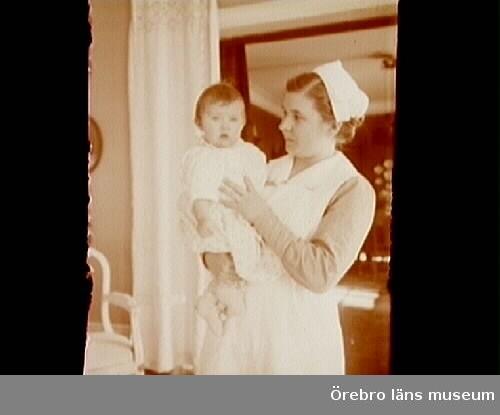 Rumsinteriör, en kvinna och en liten flicka.Barnsköterskan Annie (Titti) Wallin och Barbro Thermaenius