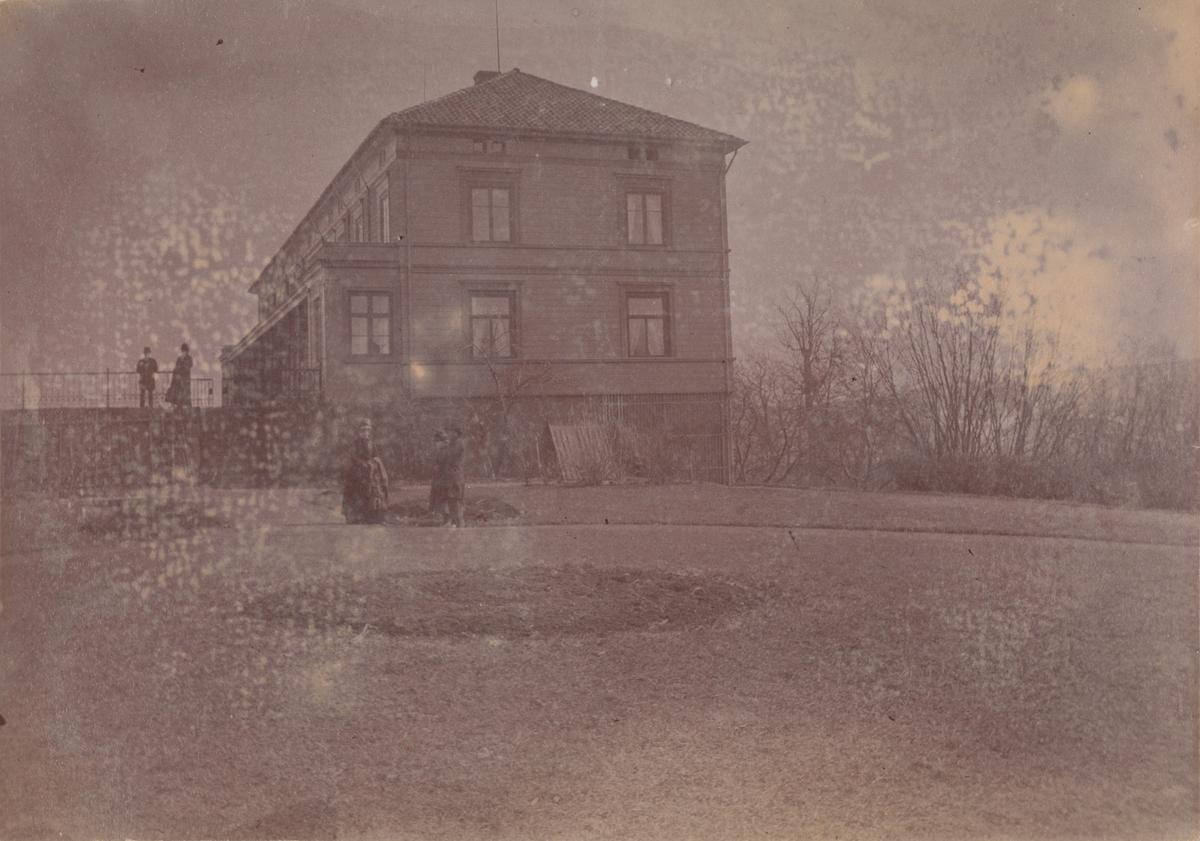 Linderud Gård hovedhus og fem mennesker sett fra den victorianske hagen.