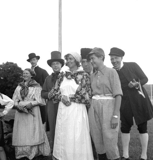 Festligheter vid Siggebohyttan den 30 juli 1937. De utklädda männen och kvinnorna deltar i någon form av dans eller teaterliknande folklustspel. Bakom dem syns en flaggstång.