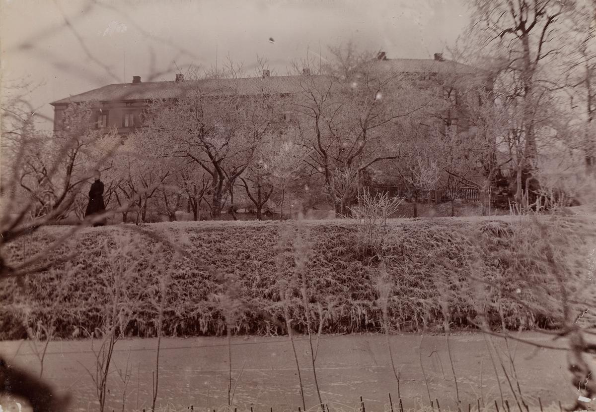 Linderud Gård hovedhus sett fra andre siden av kanalen bak hagen med frukttrær.