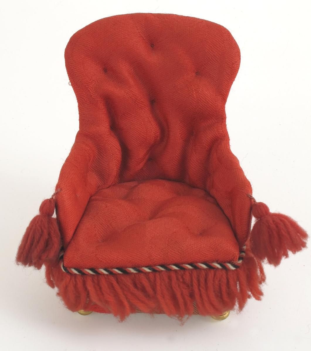 Rød ulldamask, med frynser og pomponger.  Baksiden gråmønstret rødt