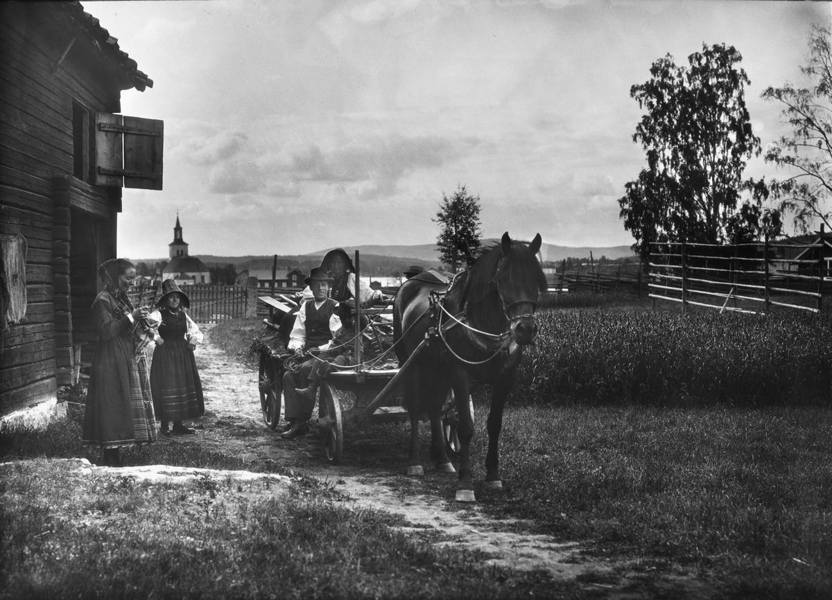 Diapostiv, fönsterbild med motiv från Floda. Tre kvinnot (kullor) i traditionsenlig dräkt, varav en sittande på kärra med man och litet barn, vilken drages av arbetshäst. Kyrka i bakgrunden.