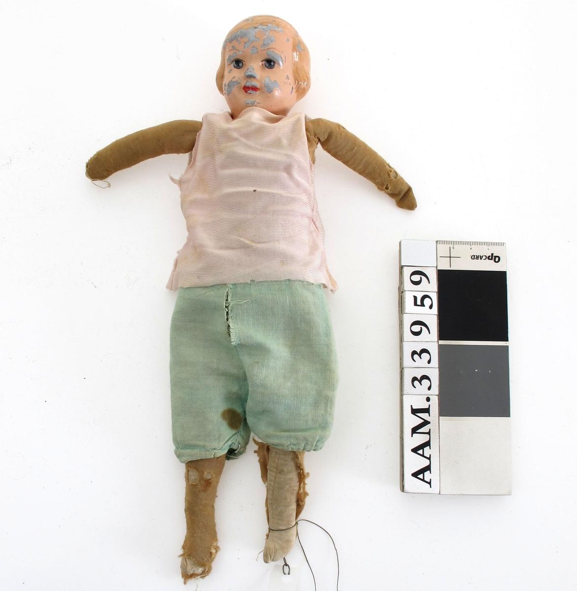 Tøydukke med støpt hode i plast (?).  Kledd i selekjole med bluse (sammensydd) og strømpebukse og underbukse.