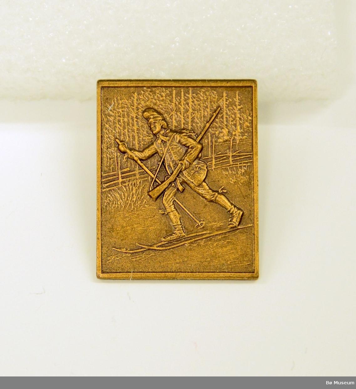 Pin - uten innskrift: I messing/kobber - bilde av en mann på ski med gevær - Jo Gjende? Med nål bakpå.
