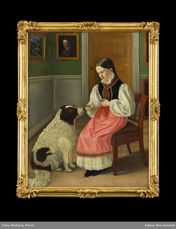 Interiörbild, i motivet centrum en flicka som sitter på en stol och matar en stor lurvig hund. Hon sitter i ett rum där man ser ett hörn av rummet med dörr, vägg med grön tapet, grå bröstning, samt tavlor på väggarna. Trägolv.