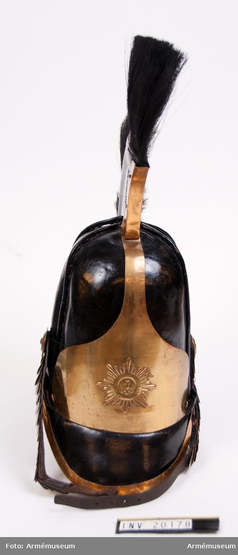 """Grupp C I. Av svart lackerat läder med svart tagelliggare och vapenplåt av mässing med Gardesregementenas stjärna. Skärm av läckerat läder med mässingsskoning. Hakrem med mässingsfjäll. Foder av grov linnelärft.  LITT  Enl. Pantschulitseffs """"Chevalier Gardets Historia"""" Del IV sidan 118 införde läderkask till Chevaliergardets uniform 1803 och var i bruk till år 1845 (Del IV sidan 128). Enl.""""Handbuch der Uniformenkunde"""", Knötel-Sieg, sidan 322, ha båda första gardeskavalleriregementerna stjärna på kasken."""