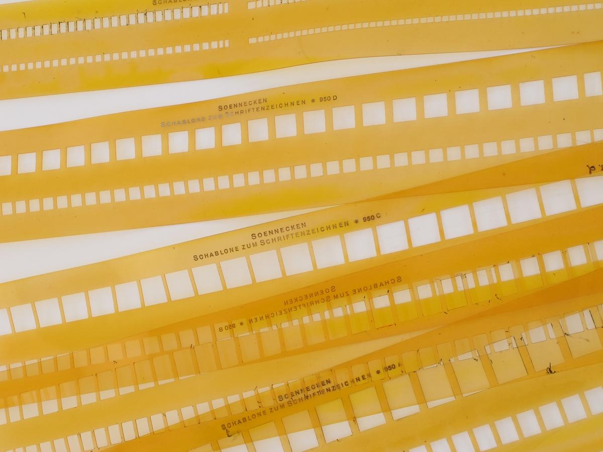 Mappe av tynn kartong med fire sjablonger av plast og en linjal av tykk kartong.
