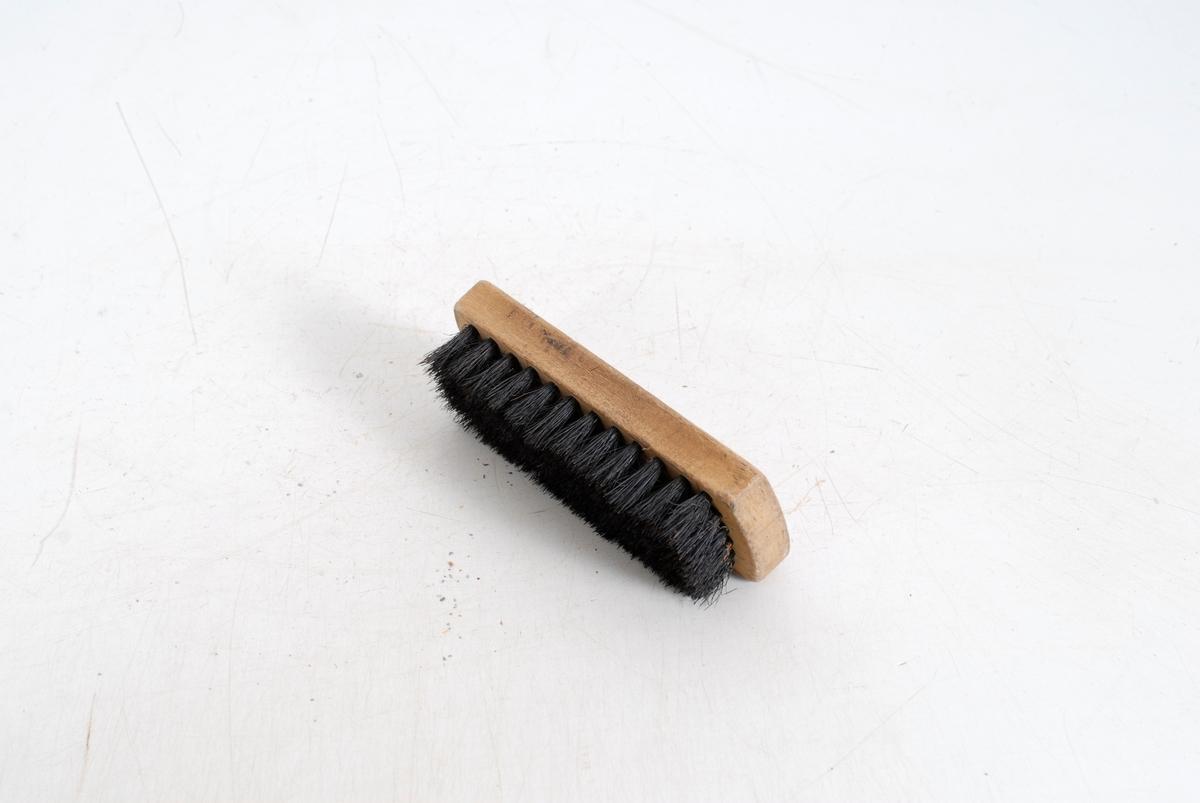 Form: rektangulær trekloss, med svart bust/ hår