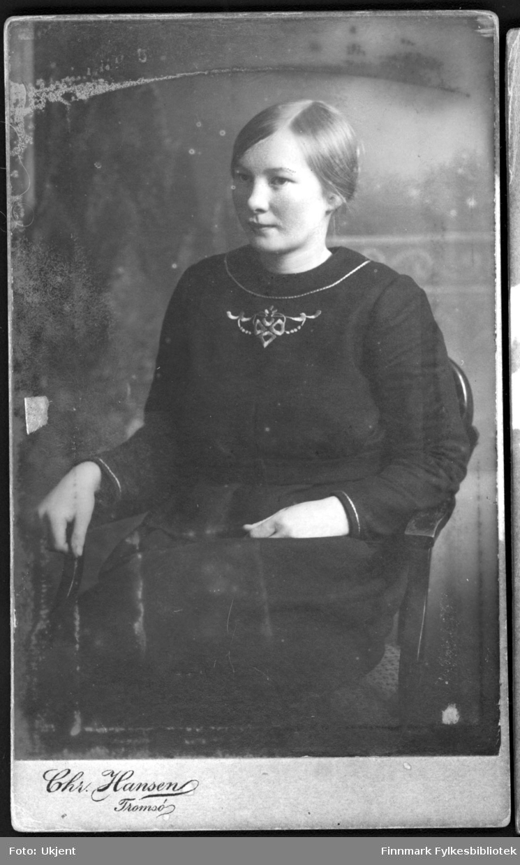 Portrett av Anna Villiamsen fra Nuvsvåg. Bildet muligens tatt på begynnelsen av 1900-tallet. Anna har på seg en kjole med en dekorativt bærestykke. Hun sitter på en stol.
