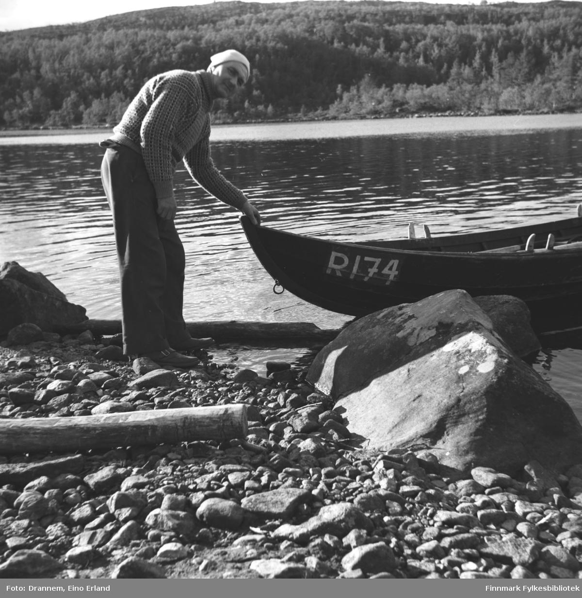 Søren Gabrielsen står foran baugen på en elvebåt ved bredden av en innsjø.