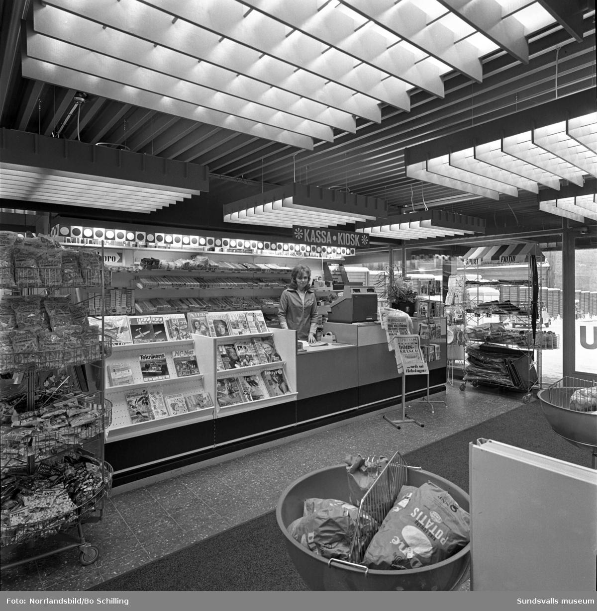 Shell bensinmack vid Rådhusgatan invid Skolhusallén, en modern mack med stort utbud av livsmedel, kläder och automater för varma och kalla drycker. Exteriör- och interiörbilder.