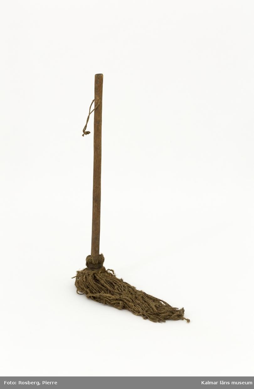 KLM 10868. Svabel. Av tvinnade snoddar fästa i omålat skaft av trä. Skaftet har hål där tunt rep i ögla är fäst igenom.