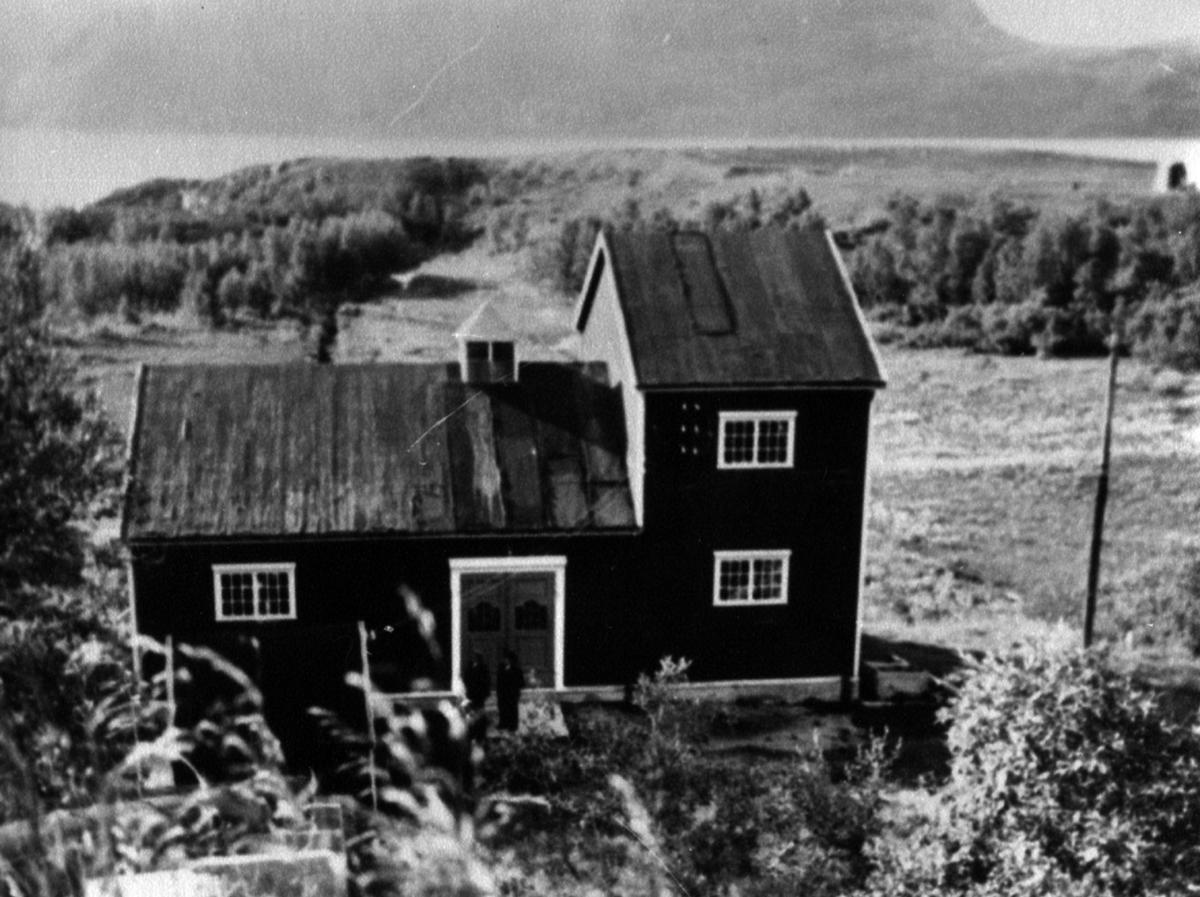 Porsa kraftstasjon i Kvalsund fotografert ca 1919. To menn står ved døren til kraftverket. Bildet er tatt fra fjellkanten ned mot bygningen