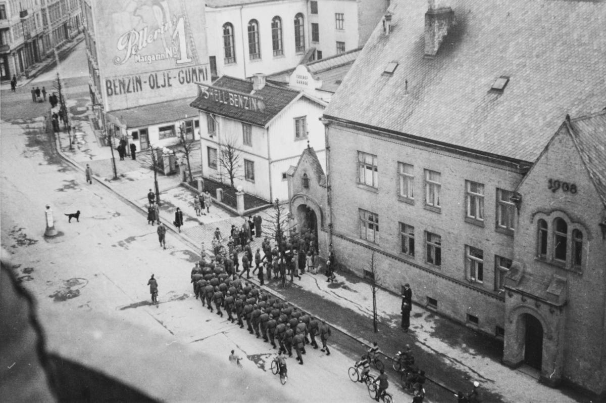 """Tyske tropper marsjerer fra Bogstadveien og inn på Majorstuen skole, som var tatt i bruk som kaserne. Tekst fra album: """"- og under sang tilbake til skolen. April 1940."""""""