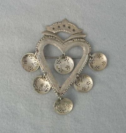 Sölja i form av ett hjärta som är ihåligt i mitten. Högst upp en kronliknande formation. Skålformade hängen med punsade blommor är fästa med en ögla på utsidan; ett längst ned och två på varje sida. Ytterligare ett hänge inuti hjärtat. Hjärtat är dekorerat med punsade små prickar längs kanten samt en bladslinga mitt på. Också överdelen har punsdekor. Ytan är matt. Det finns inga stämplar. Jfr 2231.Tillhör dräkt som fanns som modell i hemslöjdsbutiken i Kalmar.