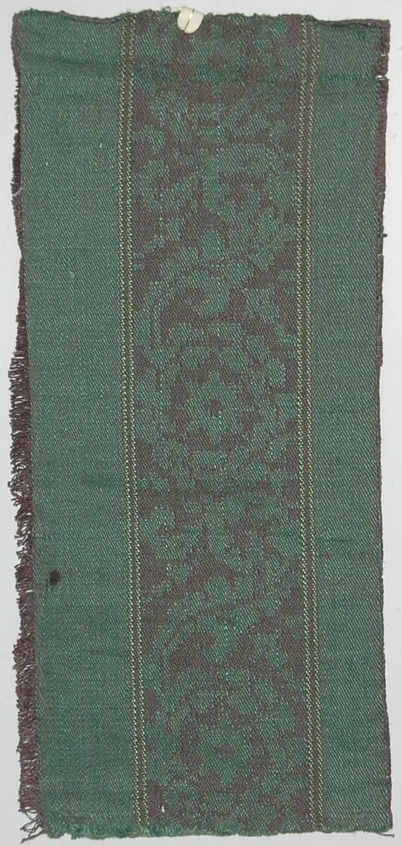 Tidigare katalogisering enl uppgift av Elisabeth Thorman kompletterad 1958 av Elisabeth Stawenow:  Möbeltyger, damast, 13 st, prover i olika färger  h) 34 x 15 cm. Varp av gråviolett merc. bomullsgarn. Väft av grönt lingarn. Enstaka inplock av grönt silke. Nr 50 i.