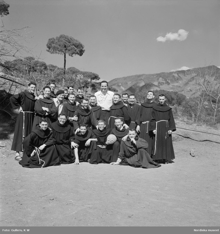 Ett lagfoto på fotbollsspelande munkar, en munk i första ledet håller i en fotboll.