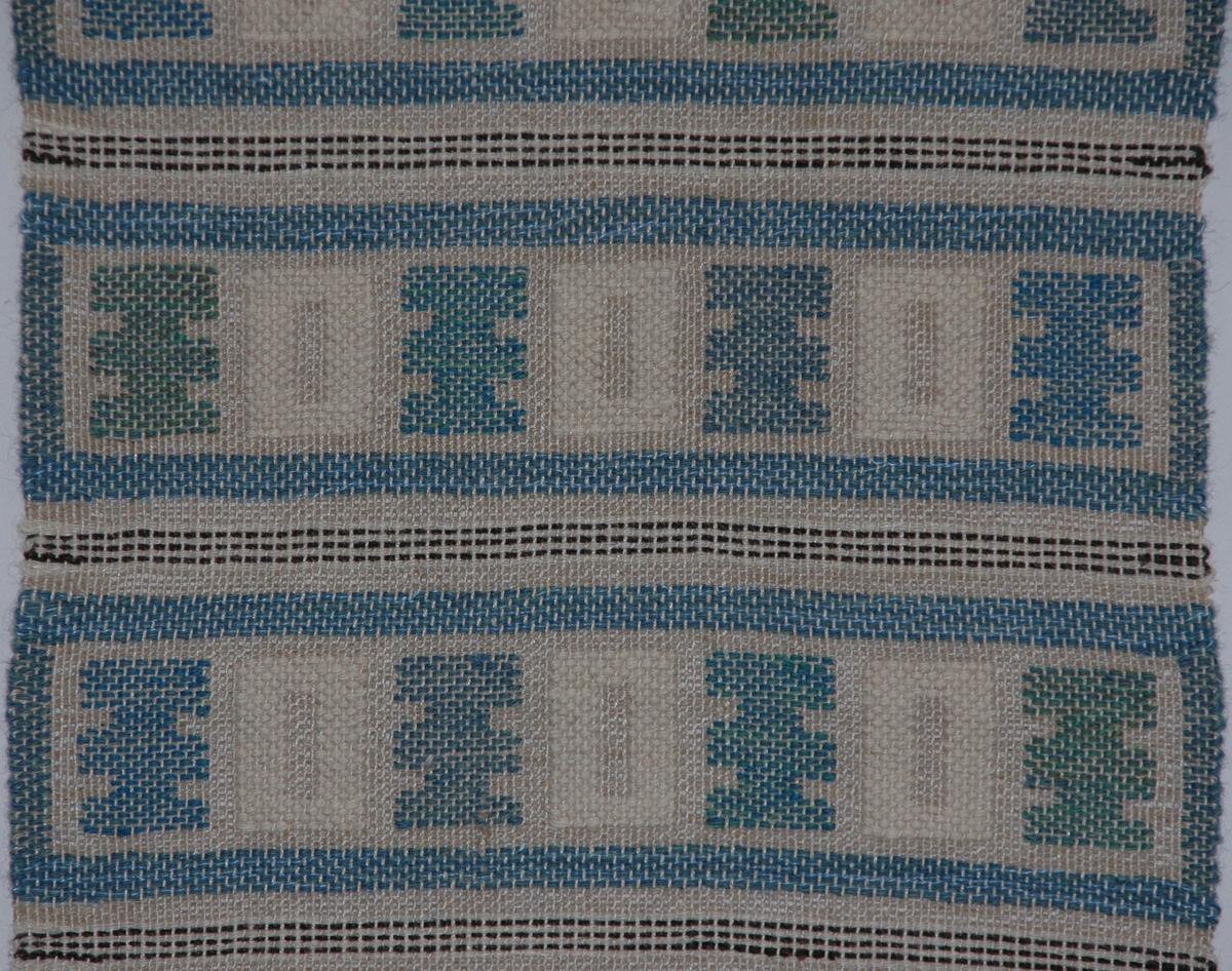 Löpare, 60 x 32 cm. Oblekt lingarn i varpen, oblekt lingarn och ylle i väften. Geometriska mönster i HV-teknik i färgerna blått, blågrönt, ljusblått, grönt, brunt och vitt. Knuten frans i kortändarna. Jämtslöjd, Östersund.  Katalogiserad av Karin Nordenfelt, Elisabet Stavenow, Marie-Louise Wulfcrona-Dagel.