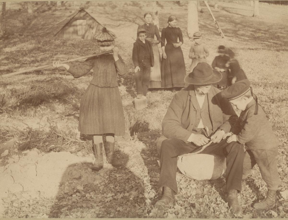 Mann og flere barn lager seljefløyter.
