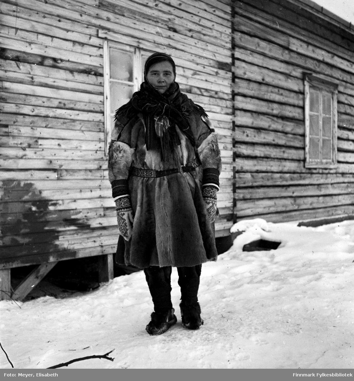 Ellen Johnsdatter Utsi fotografert utenfor en bygning. Hun har på seg samisk pesk av reinskinn, samisk vevd sjal og samisk belte, votter og lue. På føttene har hun skinnbukser og skaller med skalleband.