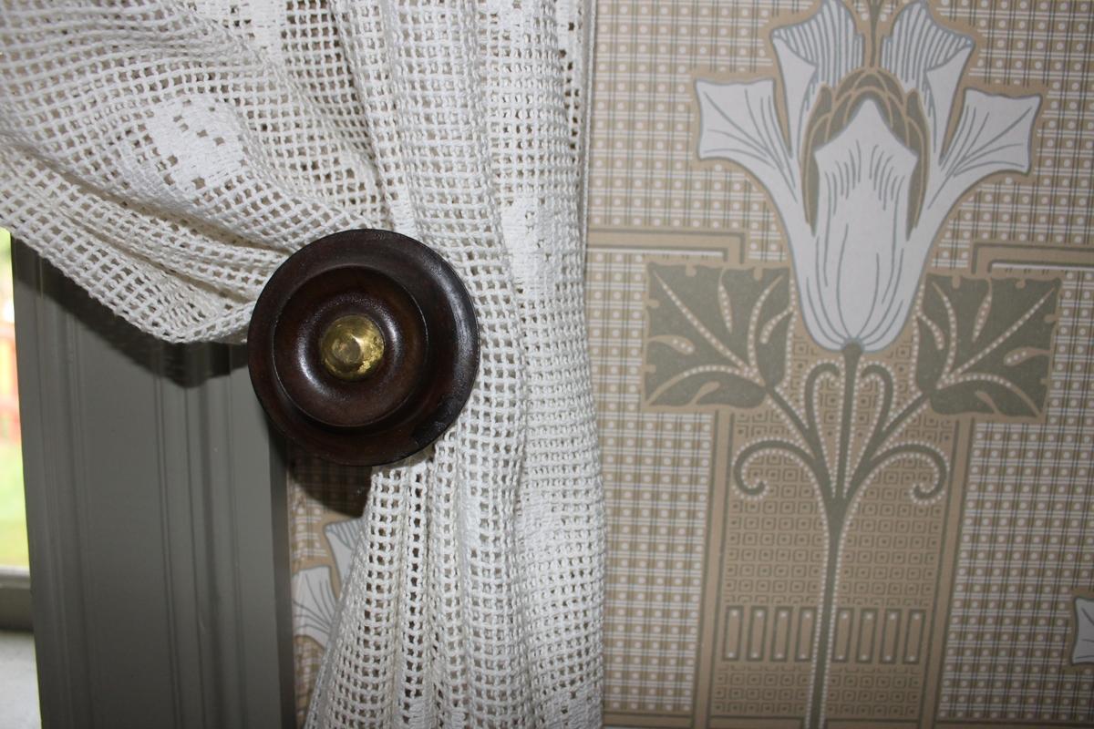 Brun gardinhållare i svarvat trä. Består av en rund träplatta med förgylld mittpunkt av mässing som är monterad på en svarvad pelare.