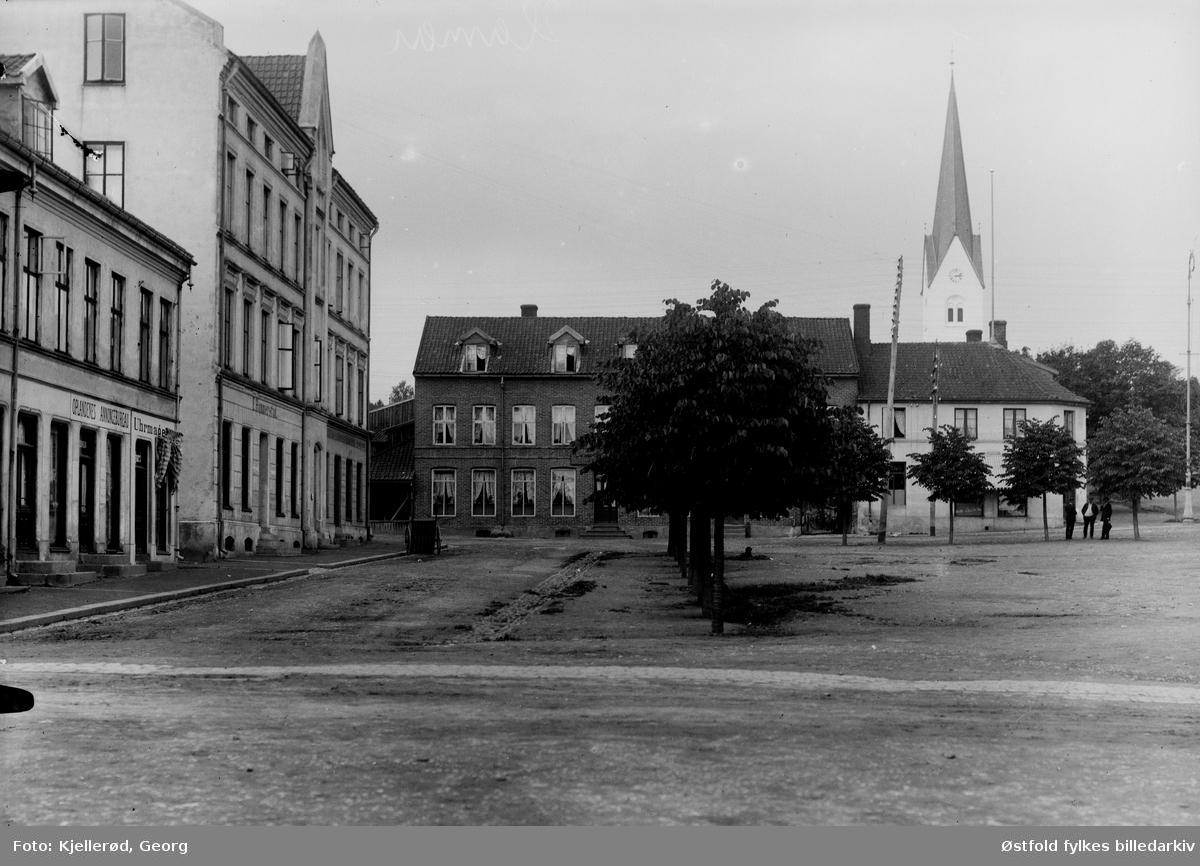 Vestre del av Stortorget i Hamar. Til venstre Oplandenes Annoncebureau og en urmaker.  Hamar domkirke i bakgrunnen. Rett frem ligger i dag Folkets Hus med Hamar kino. Til venstre ligger i dag Hamars nye kulturhus.