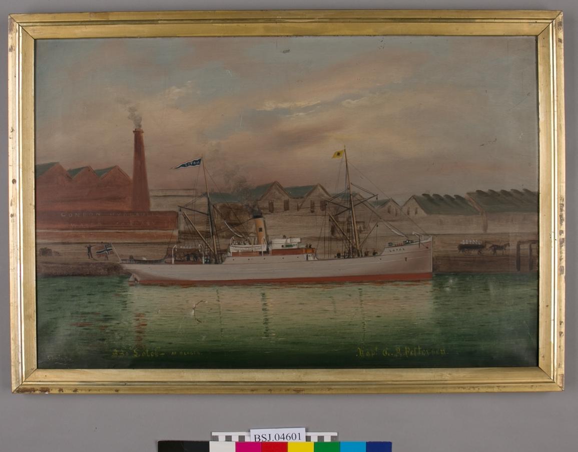 "Industrielt havnelandskap fra London, det ene bygget merket med ""London Hydraulic Water Company"". DS LOTUS ligger til kais, rigget med to master. I bakre mast vimpel med skipets navn (speilvendt), i framre mast rederiflagget til Irgens. Norsk flagg med sildesalaten i akter. Samme bakgrunnsmotiv som BSJ. 05754."