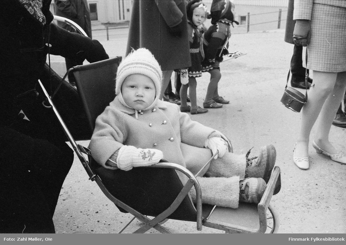 17.mai i Vadsø 1979. Fotografert av Ole Zahl Mölö. Liten gutt eller jente i sportsvogn, pyntet i dobbeltspent kåpe med gullknapper og godt kledd med nesnalobber på beina. Bak skimtes to små jenter kledd i samiskinspirerte kjoler med fine kantebånd og belter. TIl høyre i bildet ser man deler av en  kvinne kledd i tidsriktig tweed drakt  med  pumps på bena, hun holder et kamera i skinnetui i hånden.