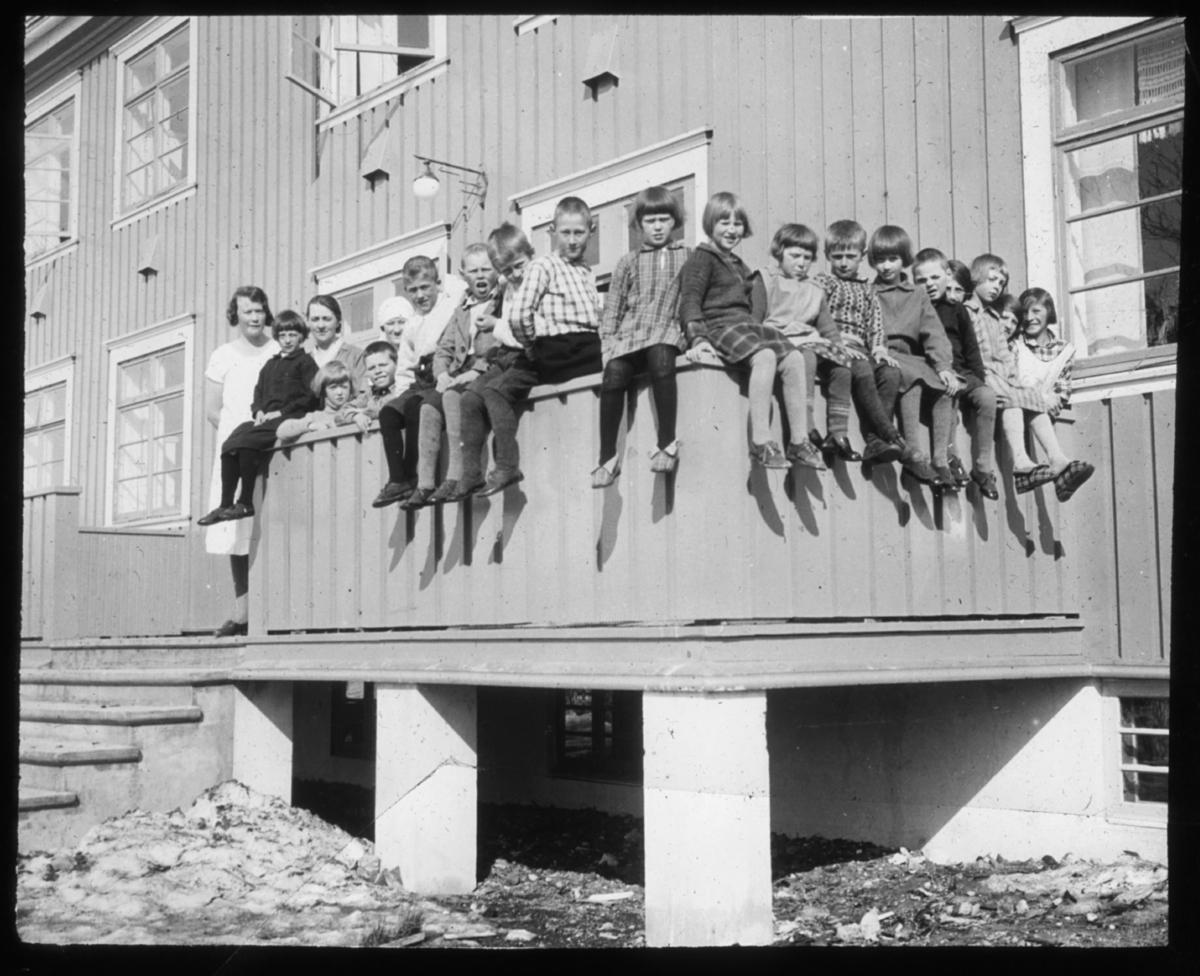 Gruppeportrett, barn. En gruppe barn er plassert på kanten av en verandra. Til venstre i bildet står det to voksne kvinner. Skolebilde eller barnehjem?