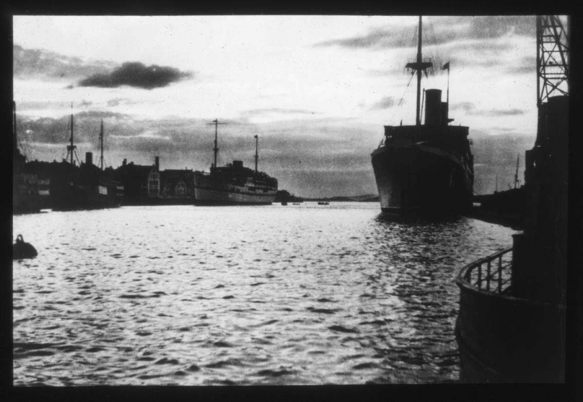 Dampskip ved kai i havn. To skip ligger til kai, skipet til høyre ser ut til å være et dampskip. Flere sjøhus ligger langs havneløpet til venstre.? En lossekran ses helt i kanten av høyre side av bildet. Begge skip har stor skorstein og ser ut til å være passasjerskip. Flere andre båter med mast ligger langs kai (skuter). Helt til venstre i bildet flyter det som ser ut til å være en fortøyningsblåse. Bildet er tatt i motlys og har høy kontrast.  Muligens er motivet fra Trondheim eller en annen nordlig by?