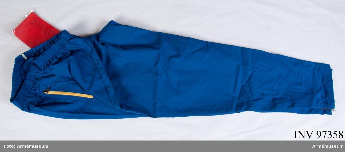 """Träningsbyxor av blå poplin med gul dragkedja. Vdihängande etikett: """"Försvarets materielverk, Originalmodell, M 7370-304000-9, Träningsbyxa poplin, 1988-09-08, Agneta Sjögren/Göran Olmarker"""". Storlek 5."""