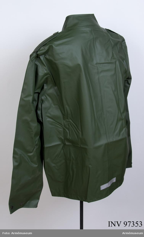 """Rock av grön PVC-belagd polyamid, med tryckknappar. Vdihängande etikett: """"Försvarets materielverk, Fastställs, M 7379-125000-7, M 7379-125000-6, Regnställ rock, 1985-11-06, (oläslig underskrift)"""". Etikett på insidan: """"M 7379-125000-7, 1985, Rukka Turo Oy, tillverkad i Finland, 80 % PVC plast 20 % plyamid, skötselanvisning, C 50""""."""