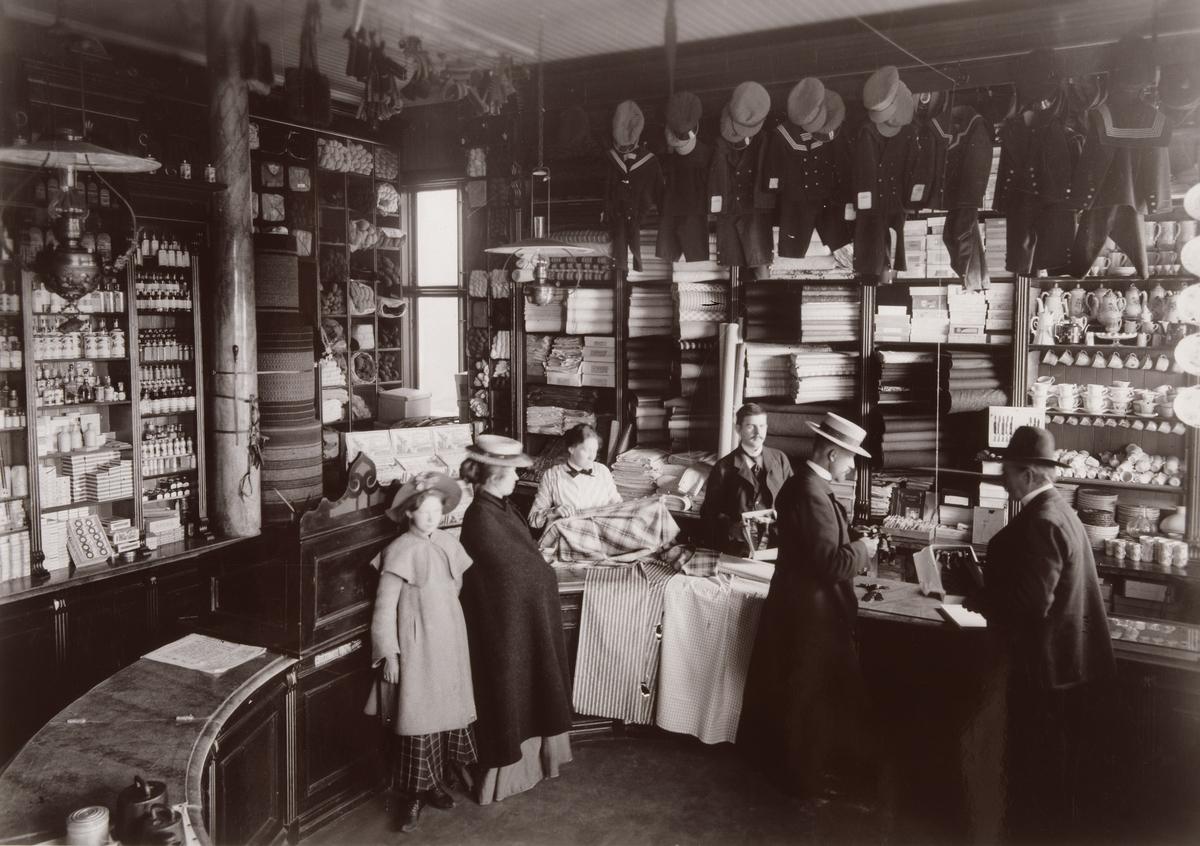"""""""Interiör från Greens affär i Kiruna 1903.Kunder och expediter på var sida om disken En mängd olika varor exponeras på hyllor och krokar."""""""