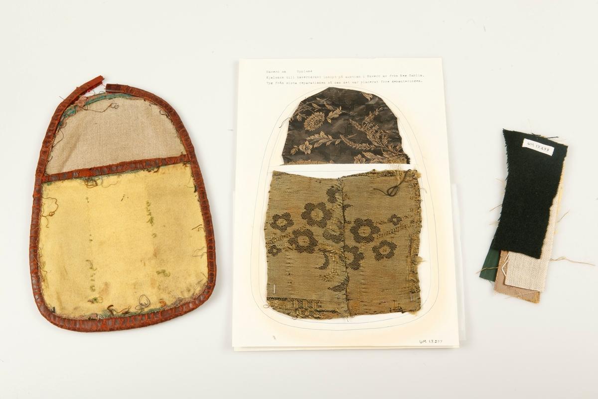 Demonterad kjolsäck till Häverödräkt. Skinnkantad med bakstycke av grå linnelärft och framstycke av gult ylle i satinbindning. På baksidan grönt tuskaftat ylletyg. Runt skinnkanterna rester av ursprungligt nu bortklippt tyg. Två pappersark med det tyg från sista reparationen som satt på väskan vid förvärvet. Bakstycket av siden mönstrat i svart och gult och framstycke av halvsiden i gult och svart. Väskan har undersökts av Bo Peterzon 1967, se bilaga UM 17.299. Tygprover i rött skinn, grönt ripssiden, gulbrunmönstrat siden, gul yllesatin, grå linnelärft, mörkgrönt tuskaftat ylle.