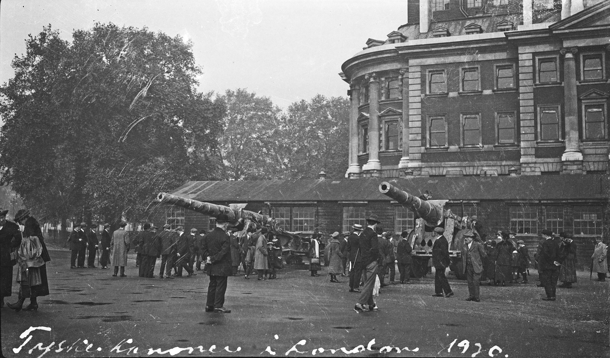 Krigsbytte. To tyske kanoner utstillt i London. Mange interesserte tilskuere. Større bygning/slott. Større park i bakgrunnen. Hverdagsbilde.