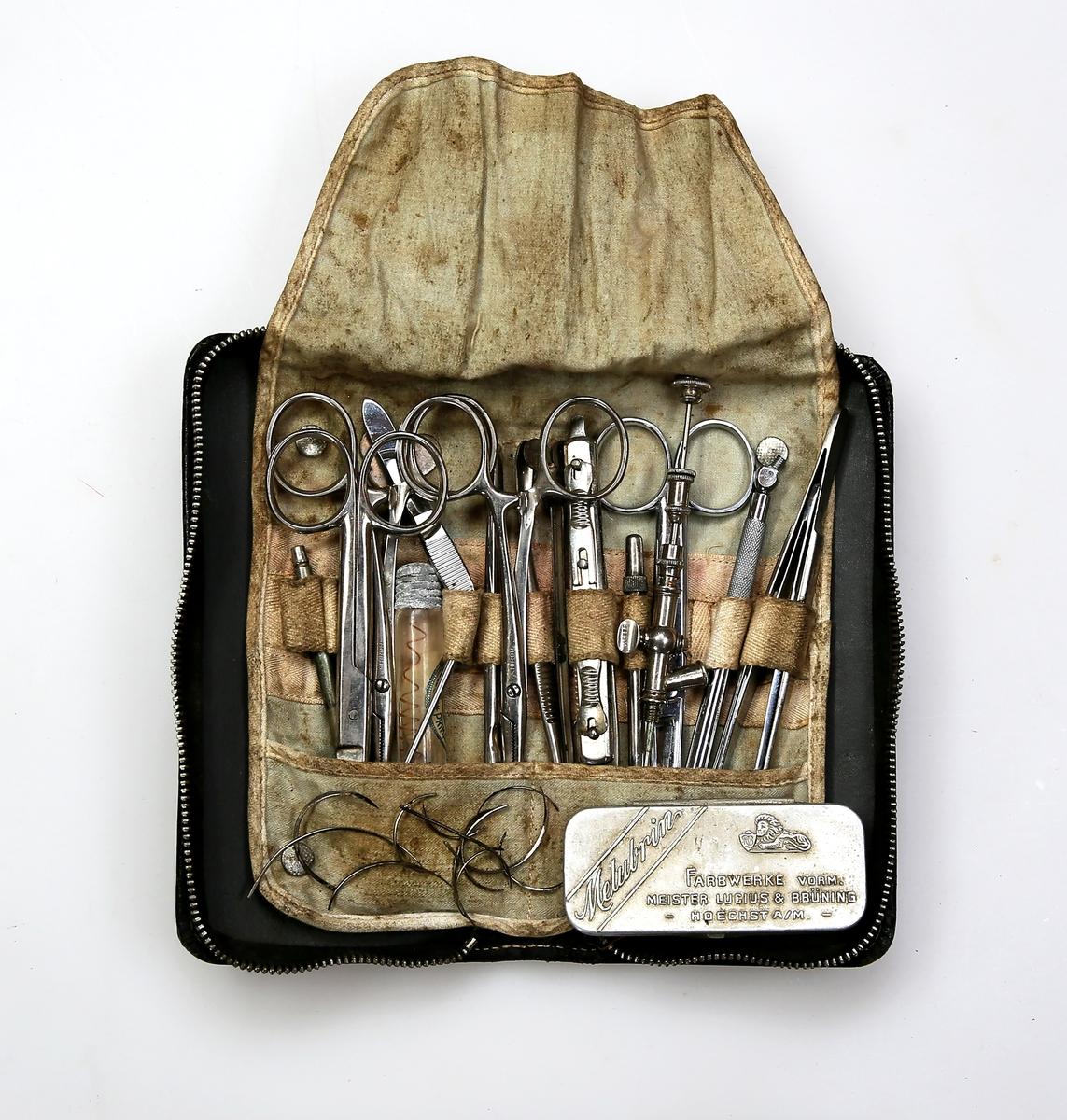 Skinnetui med diverse instrumenter for mindre kirurgiske inngrep og skadebehandling, herunder sakser, kniver, pinsetter, suturnåler, suturtråd, nåleholder, injeksjonsnåler